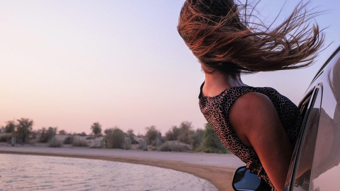 menina com vento no cabelo na praia