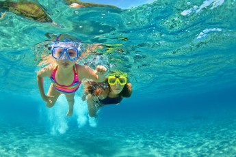 Mãe e filha mergulhando / foto: Denis Moskvinov - Viajar sozinha com filho