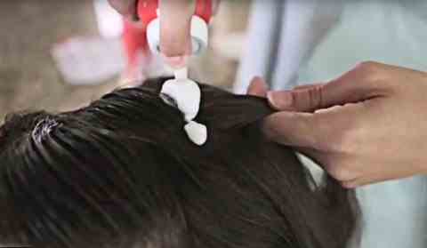 Applying Vamousse to a section of hair