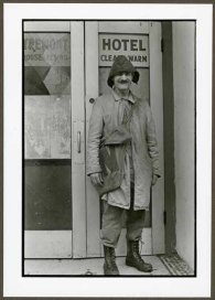 "VPL 88653 ""Man in coat and hat standing outside hotel entry"". Nina Raginsky. 1972."