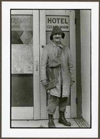 "VPL 88653 ""Man in coat and hat standing outside hotel entry"". Nina Raginsky. 1972."