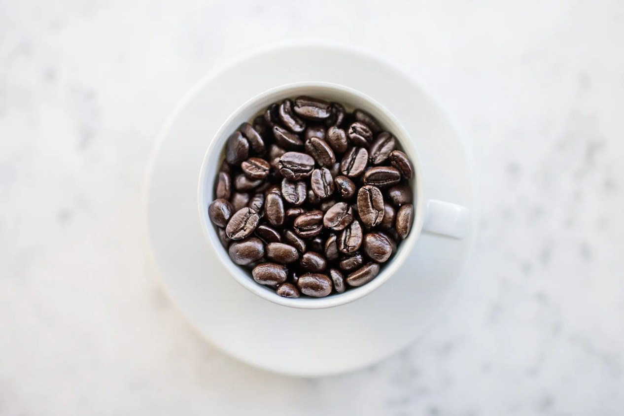 Photograph of coffee beans inside a coffee cup