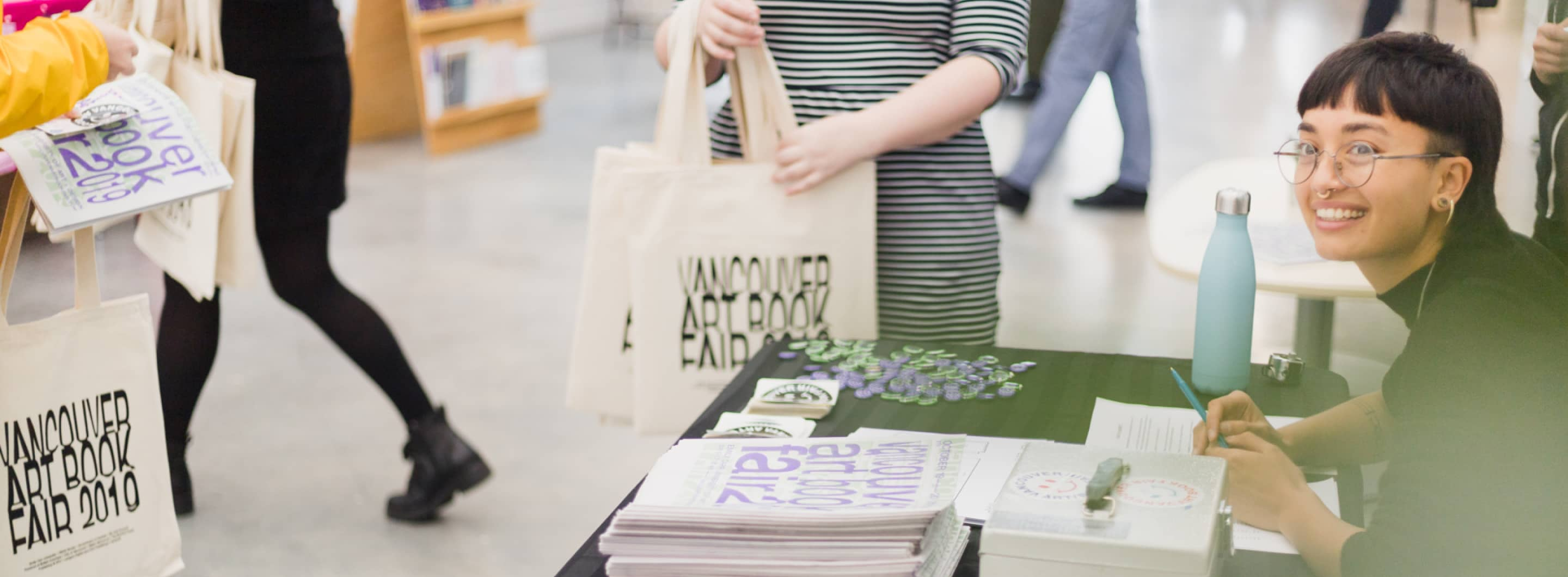 Photograph from VABF 2019 of the Vancouver Art Book Fair membership table, volunteers give away free totes to attendees.