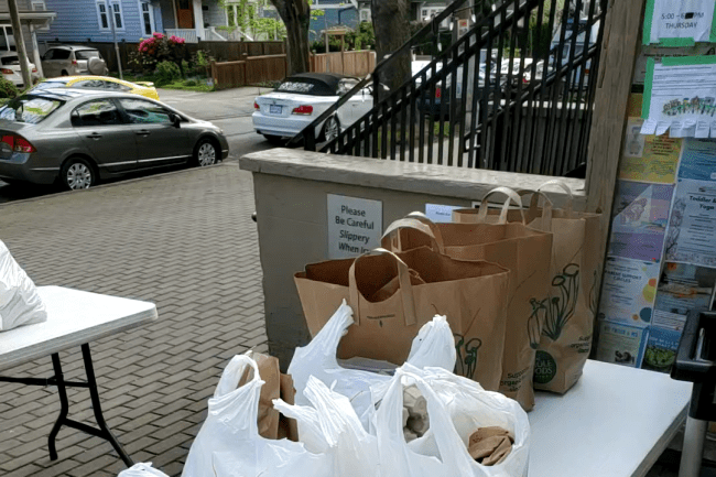 An outdoor image of Kitsilano Neighbourhood House, showing tables filled with grocery bags.