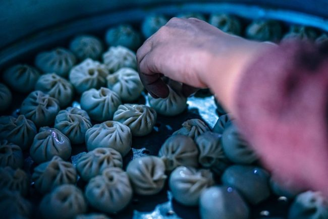 An image of a person forming a large batch of Chinese dumplings.