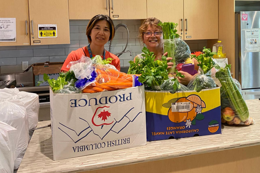 An image of two women smiling while packing boxes full of fresh, brightly coloured produce
