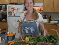 An image of Laura wearing an apron and smiling in a kitchen full of food in wicker baskets