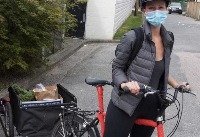 An image of a volunteer wearing a mask as she prepares to make deliveries by bicycle