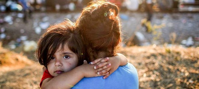 A young Syrian migrant girl is held by her mother next to railroad tracks where migrants wait to cross into Macedonia Sept. 2, in Idomeni, Greece. The number of people leaving their homes in war torn countries such as Syria, marks the largest migration of people since World War II. (Win McNamee/Getty Images)