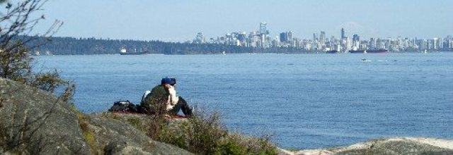 Couple on rocks admiring Vancouver from Lighthouse Park