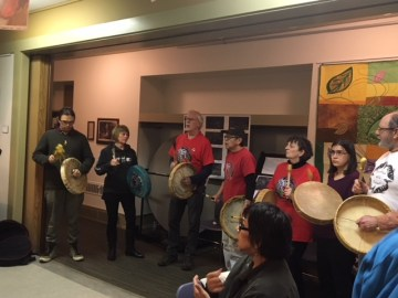 Drumming at Hewett Hall: Stó:lō Elder from the Skwah First Nation and president of Wild Salmon Defenders Alliance, Eddie Gardner (middle red shirt), leads drumming
