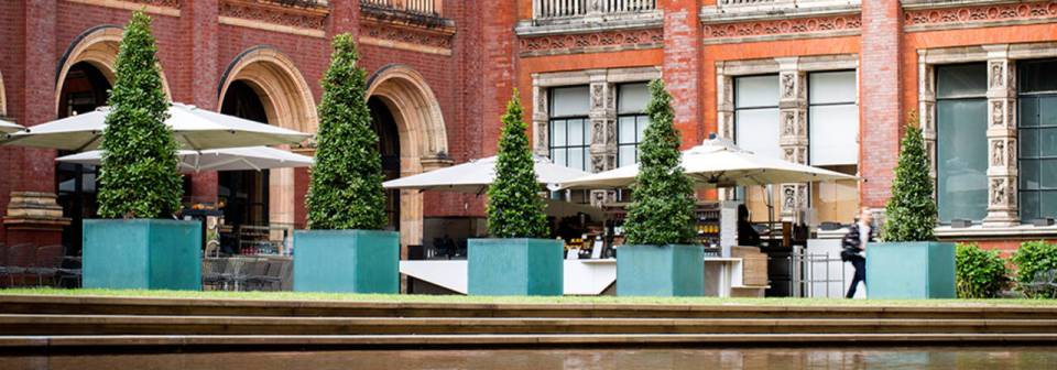 V&A garden cafe, with tables and chairs under umbrellas near trees and water feature