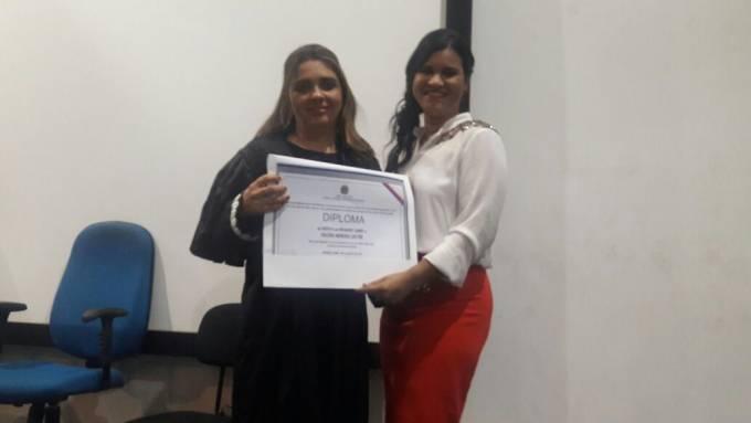 Valéria recebendo o diploma das mãos da Dra. Lavinia.