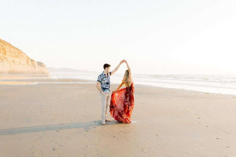 Engaged Couple walking on the beach at Torrey Pines, California
