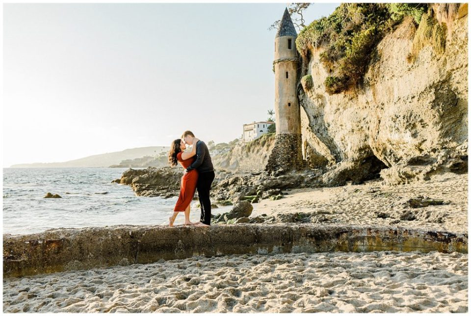 engaged couple kissing at beach