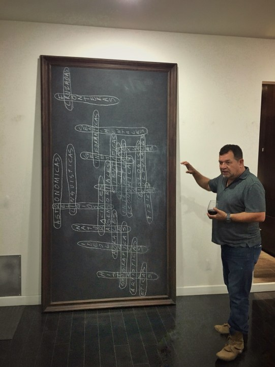 Erre explaining his piece Cruzadas Fronteras, a blackboard of concepts that analyzes border crossing. It was exhibited with erasers printed with the words: love, education, freedom, and justice, meant to playfully erase the conceptual borders.