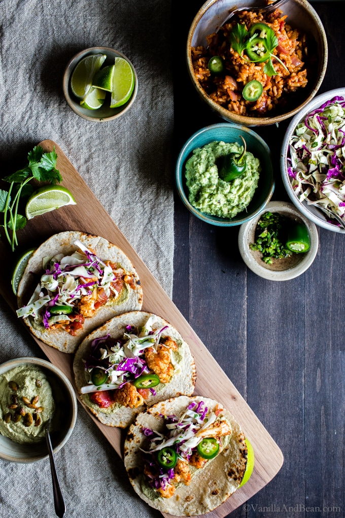 A weeknight staple, Roasted Cauliflower Tinga Tacos with Chili-Lime Slaw are chipotle spicy, and packed with flavor. These vegan tacos freezer friendly and done in about 30 minutes! Serve with your favorite Mexican inspired sides and don't forget the guacamole! #vegan + optionally #glutenfree  #Tacos #recipe #Vegetarian