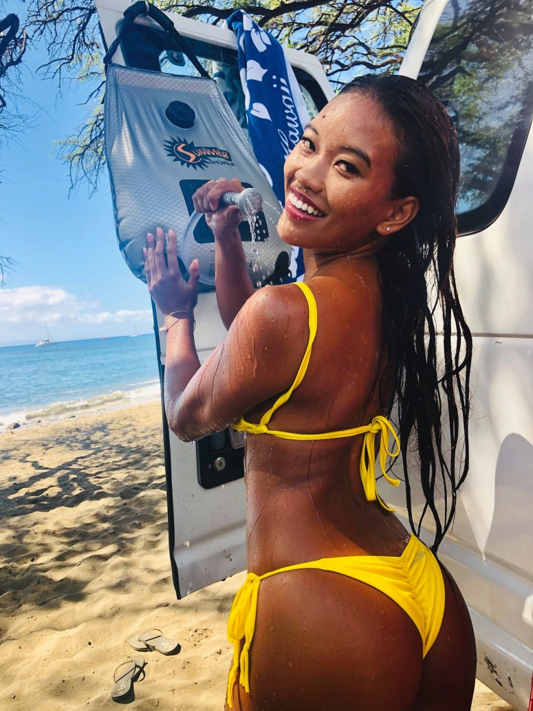 outdoor portable solar camping shower hose in bikini on the beach in maui rent a campervan vanlife fully equipped affordable price