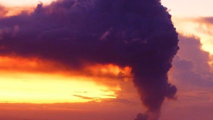 The cloud formation above Mt Yasur Volcano on a clear morning on Tanna Island, showing a magestic dark purple hue contrasting sharply with the tropical Vanuatu sunrise, presenting a fantastic spectacle