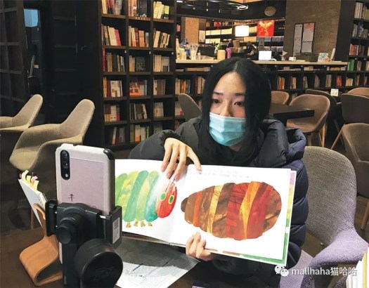 A Zhongshuge bookstore employee reads a book via livestream in Shanghai earlier this month. [Photo by Niu Jing/For China Daily]