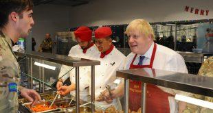 Boris Johnson skammtar breskum hermönnum í Eistlandi jólamatinn.
