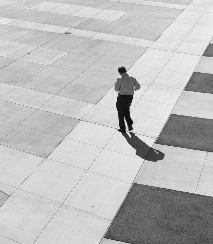 Black and white photograph of a man walking through an empty plaza, the instant captured in the photograph makes it look like the figure is dancing alone.