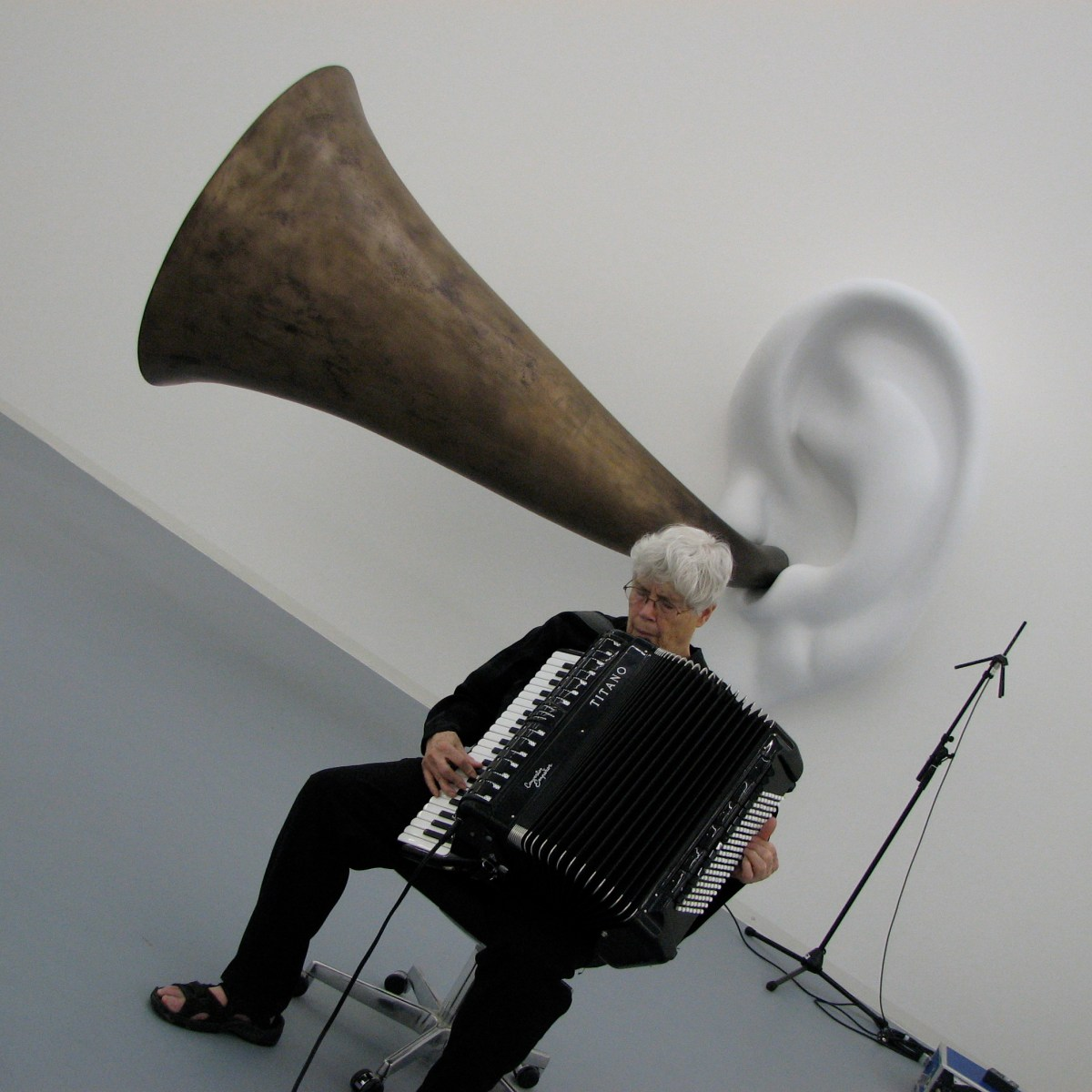 An image of composer and musician Pauline Oliveros performing. The orientation of the image is skewed, so the floor is slanted and angles down to the right. Oliveros sits on a chair with a large accordion, her head is tilted down, her eyes are closed, and she has an expression of deep concentration. Oliveros sits in a large gallery room, and behind her there is a giant white ear on the wall with a huge, brass ear horn.