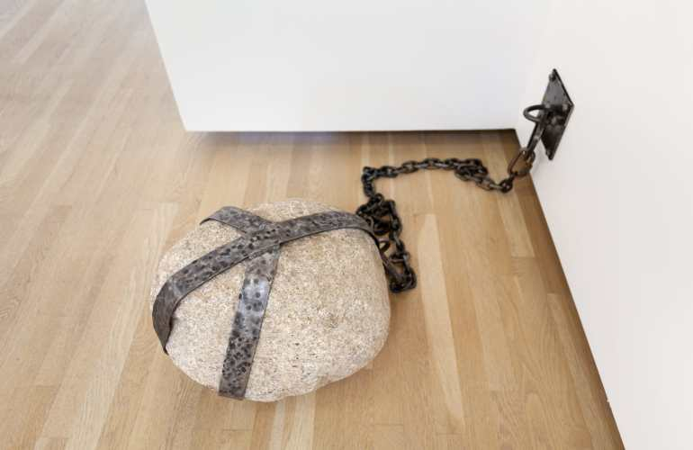 An installation photograph of an artwork by Fay Ray, which consists of a large, light brown, oval rock tethered to the wall with a heavy metal chain, and bound by a hammered metal cage.