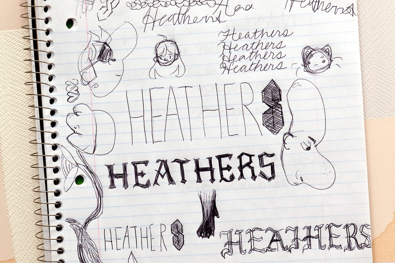 """A photograph of a spiral bound notebook with the word """"Heathers"""" drawn all over the page in different fonts with other doodles."""