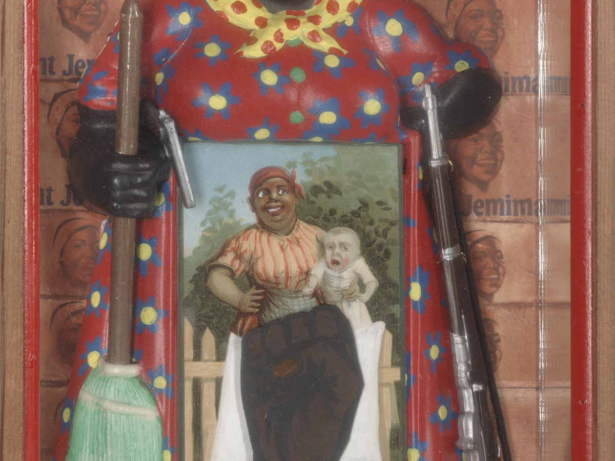 """A shallow, rectangular box containing a figurine of the racist caricature Aunt Jemima. In one hand she holds a broom and a pistol, in the other hand she holds a rifle. A postcard of the racist """"mammy"""" caricature holding a white baby covers the Aunt Jemima doll's lower body. A Black power fist covers the lower body of the mammy figure in the card. The Aunt Jemima doll stands on a bed of fluffy white cotton. The back of the box is covered with a grid Aunt Jemima logos."""