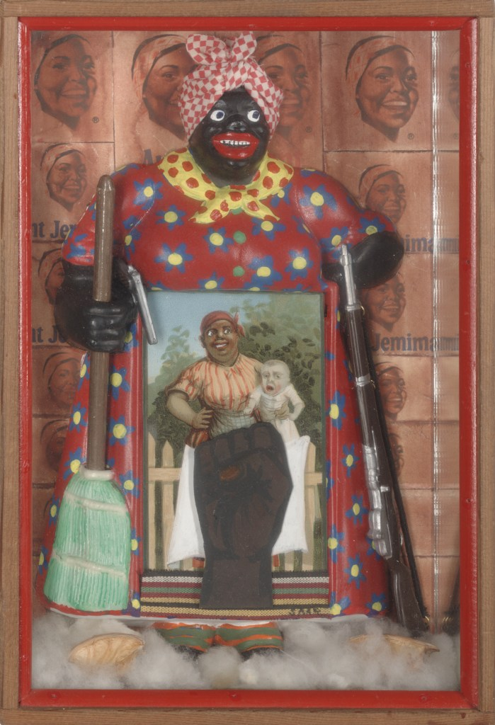 "A shallow, rectangular box containing a figurine of the racist caricature Aunt Jemima. In one hand she holds a broom and a pistol, in the other hand she holds a rifle. A postcard of the racist ""mammy"" caricature holding a white baby covers the Aunt Jemima doll's lower body. A Black power fist covers the lower body of the mammy figure in the card. The Aunt Jemima doll stands on a bed of fluffy white cotton. The back of the box is covered with a grid Aunt Jemima logos."
