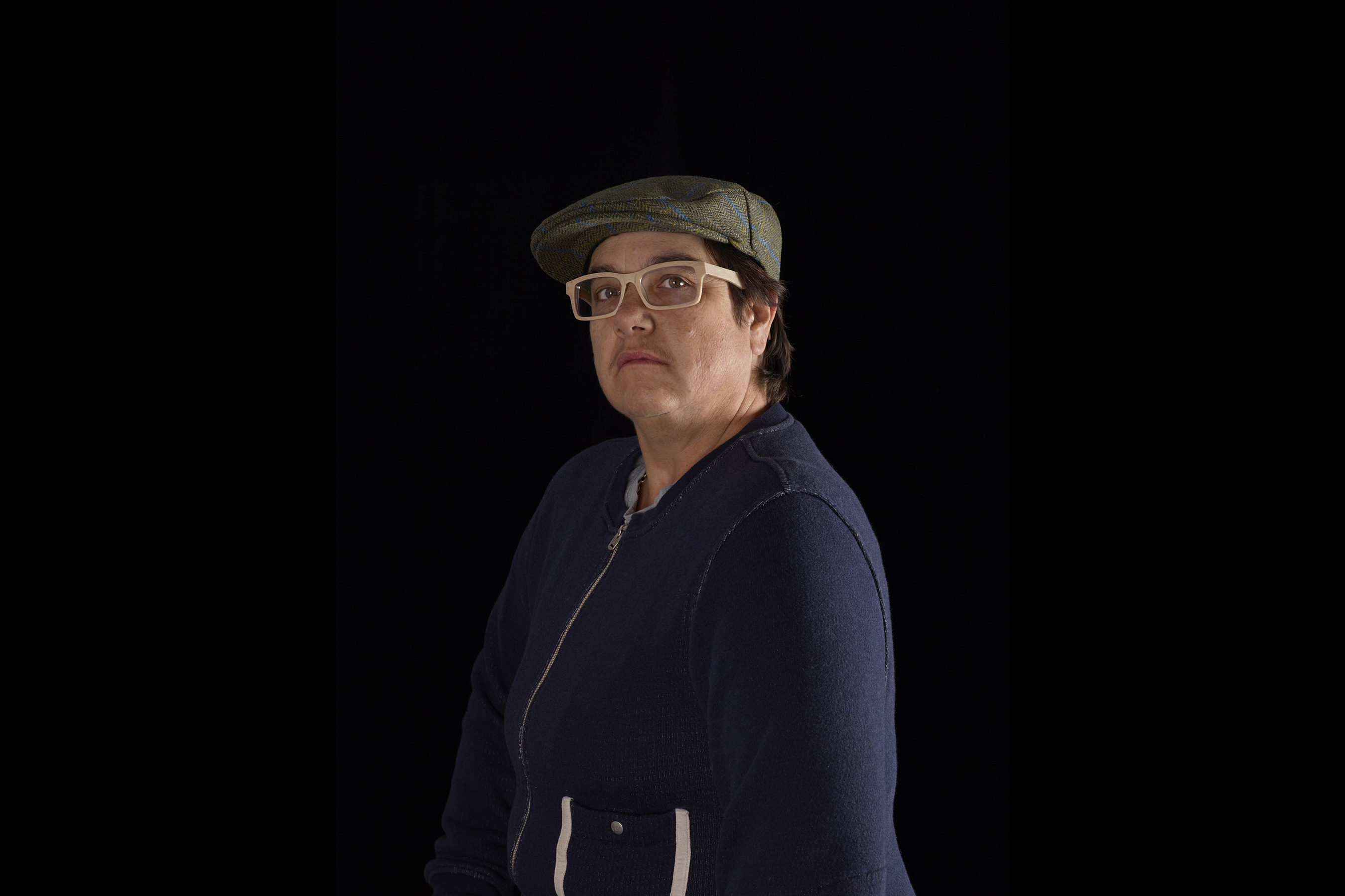 A portrait of the photographer Catherine Opie, showing a three-quarter view of her upper body on a black background. Her eyes look into the lens. Opie has short brown hair, and is wearing a dark blue sweater with a zipper, a wool cap, and beige glasses.