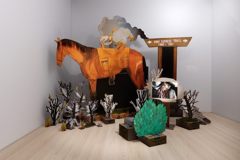 "An installation image of a sculpture by Christina Corfield. Cut out maquettes of a horse with a western saddle, small black shrubs, a small green bush, a sign that reads ""Pony Express Trail 1860–1861,"" and a smokey cloud with a hand reaching down toward the horse, all crowd in the corner of a room."