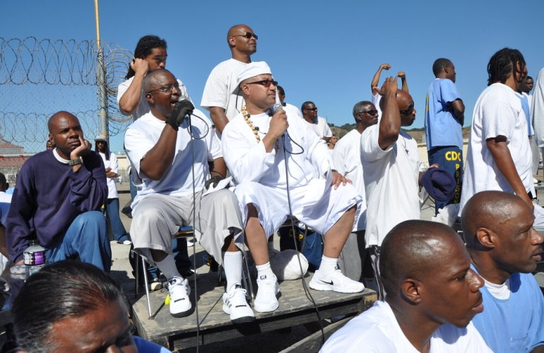 A photograph by Eddie Herena, made while he was incarcerated at San Quentin Prison. The picture shows a group of incarcerated men, two sitting on a platform holding microphones, the rest standing around them. Everyone is looking to the right, some are wearing all white, others are wearing all blue, or blue and white, the colors perfectly match the clear blue sky above them. There is a chain link fence with barbed wire on its top edge on the left side of the photo.