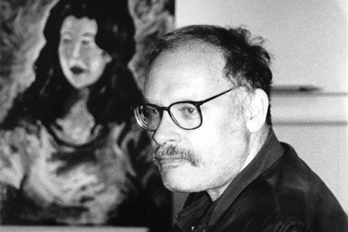 A black and white photograph of filmmaker George Kuchar. He sits with his body turned perpendicular to the camera, his face is in three-quarter profile. He has a mustache, glasses, and thinning hair. Behind him, a portrait of a woman hangs on the wall.