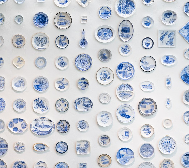 Nearly one hundred ceramic plates hanging on a white wall, each with a unique illustration of Death Row Inmate's last meals in blue.
