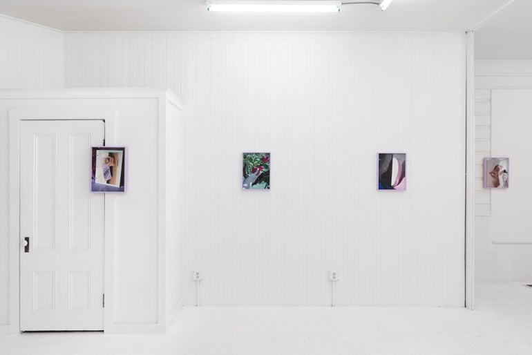 "Installation view of ""Notions"" by Melanie Flood. Small color photographs in lavender frames hang on the white walls of a room, one overlaps a door frame."