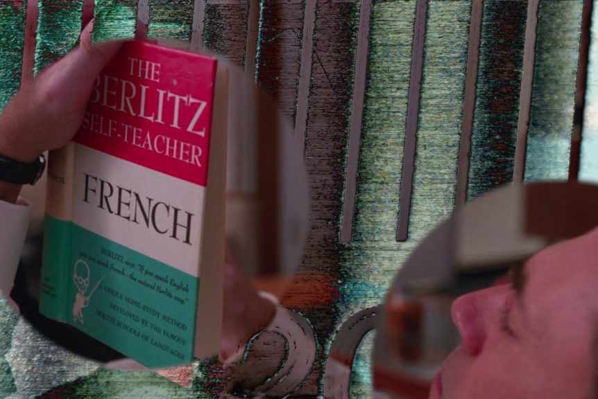 "A film still showing a collage of scenes. Two circles show one scene of a light skinned man reading The Berlitz Self-Teacher textbook ""French."" One circle floats slightly left of the center, while the other recedes into the lower right corner. The background is abstract shapes and colors, mostly green, grey, and black."