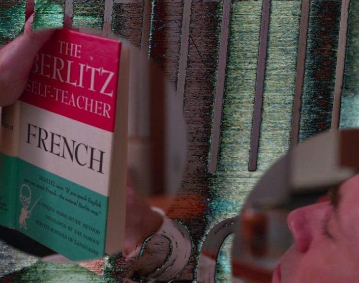 """A film still showing a collage of scenes. Two circles show one scene of a light skinned man reading The Berlitz Self-Teacher textbook """"French."""" One circle floats slightly left of the center, while the other recedes into the lower right corner. The background is abstract shapes and colors, mostly green, grey, and black."""