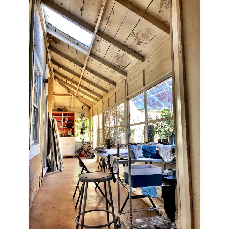 A photograph of an artist studio set up in a sunny, long and narrow room with skylights.