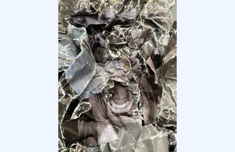 A color photograph of a black and white printed image crumpled and crushed so the original image is entirely destroyed, except in the center where an open mouth is mostly visible. The ink on the paper has worn off at the edges of the creases, leaving stark white lines.