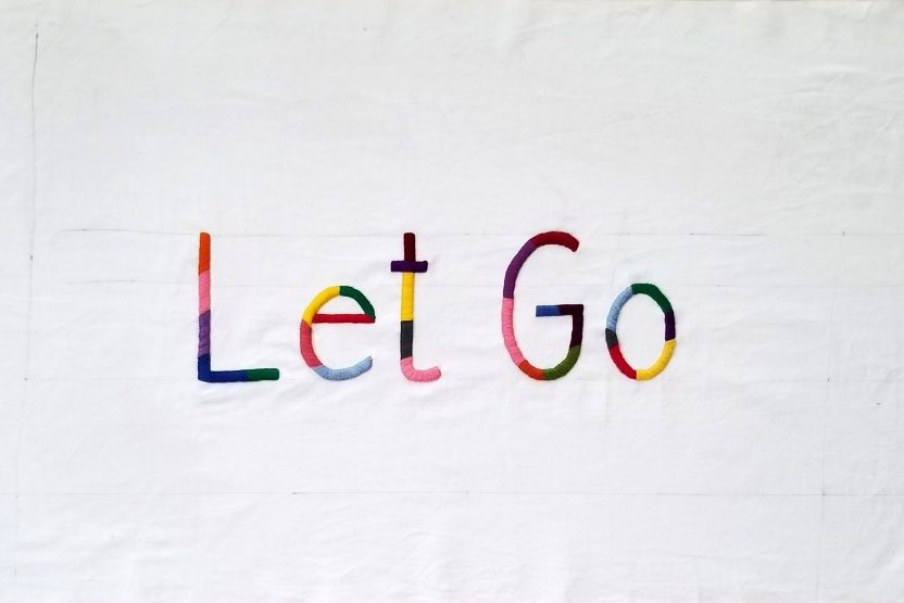 "White, hand-spun cotton fabric with large, hand-embroidered text in the center that reads ""Let Go."" The text is in simple, sans serif letters with variously sized stripes in a rainbow of colors."