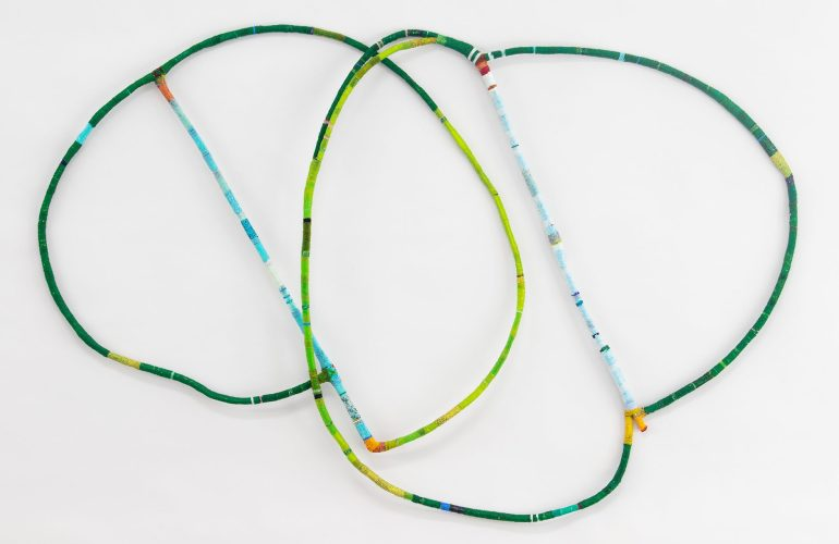 Two large, thin shapes made of bend wood wrapped with tiny beads. The shapes are overlapping, and each shape is like two circles of different sizes joined together by a bar across their diameter. The beading is in shades of green, and the central line is light and bright blues. The joints are orange, red, and yellow.