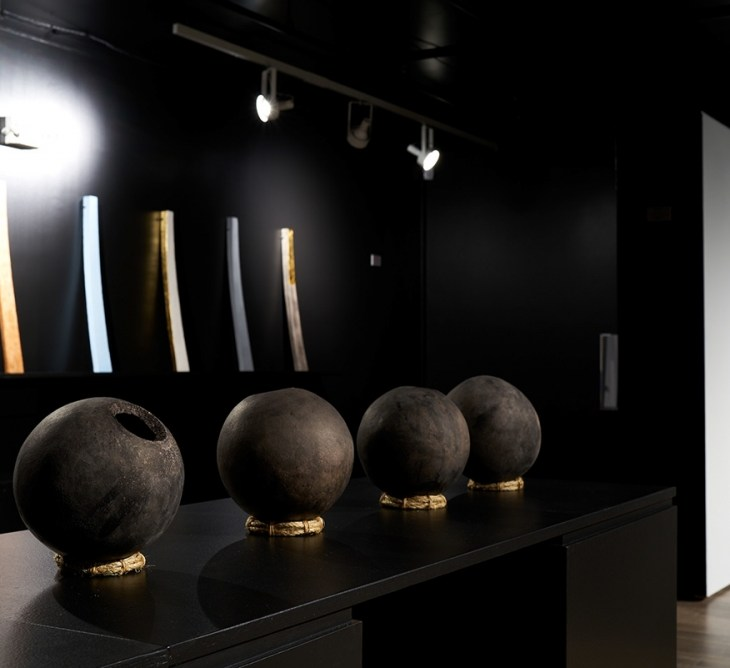 An installation image of Christopher Shaw's sculptures. Four dark brown, spherical ceramic sculptures sit on woven grass trivets on top of a black plinth. The wall behind them is also black. It has a long shelf that supports six long, rectangular sculptures that have a slight concave bow to their shape. Each sculpture is painted in different colors. On the right edge of the image, there is a white wall showing more of the exhibition.