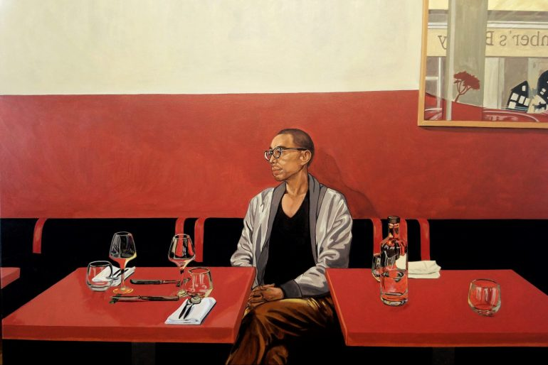 A realistic painting of a man with a shaved head and glasses sitting in a restaurant. He's sitting on a wall of upholstered benches that are black with red stripes staggered along the top of the backrest. The tables are small with a red tabletop. The man looks to the side with a calm expression. The lower half of the wall behind him is red, the top half is beige. There is a mirror on the wall to the right of the painting reflecting the street scene outside.