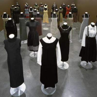 A room with brown walls and grey cement floors filled with headless female mannequins wearing various outfits for a range of seasons. The colors are primarily black and white, with a few yellow, brown, grey, and red garments.
