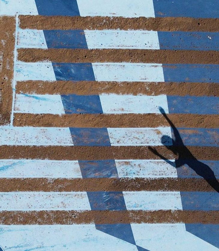 A scene filmed from a flying drone looking down on a large US flag design made out of brown soil. The flag consists of a large rectangle of soil in the upper left corner and seven long stripes of soil mimicking the flag's stripes. Under the soil are irregular stripes of light and dark blue. In the lower right corner of the image a person is dancing. The body's shadow extends diagonally toward the upper right corner. The person's arms are raised.