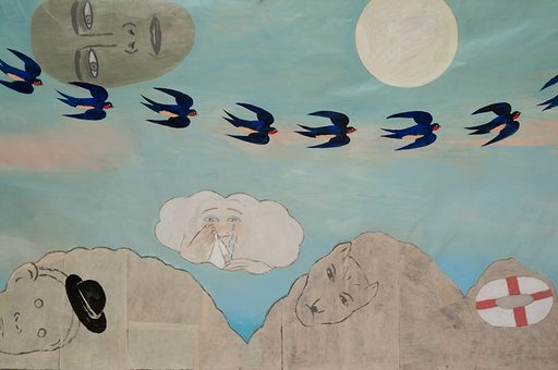 A dreamlike illustration on paper. A blue sky with wispy white and peach clouds creates the background. A mask-like face floats on the left half of the upper edge, looking down. There is a curved row of eight sparrows flying across the sky. A full moon hangs on the right half of the upper edge. The bottom has three light grey mounds. One mound has a cartoonish face with a black bowler hat. The second mound has the face of a large cat. The third and smallest mound has a lifesaver/buoy. Between the two larger mounds, a crying person holding a tissue to their eye floats in a cloud.