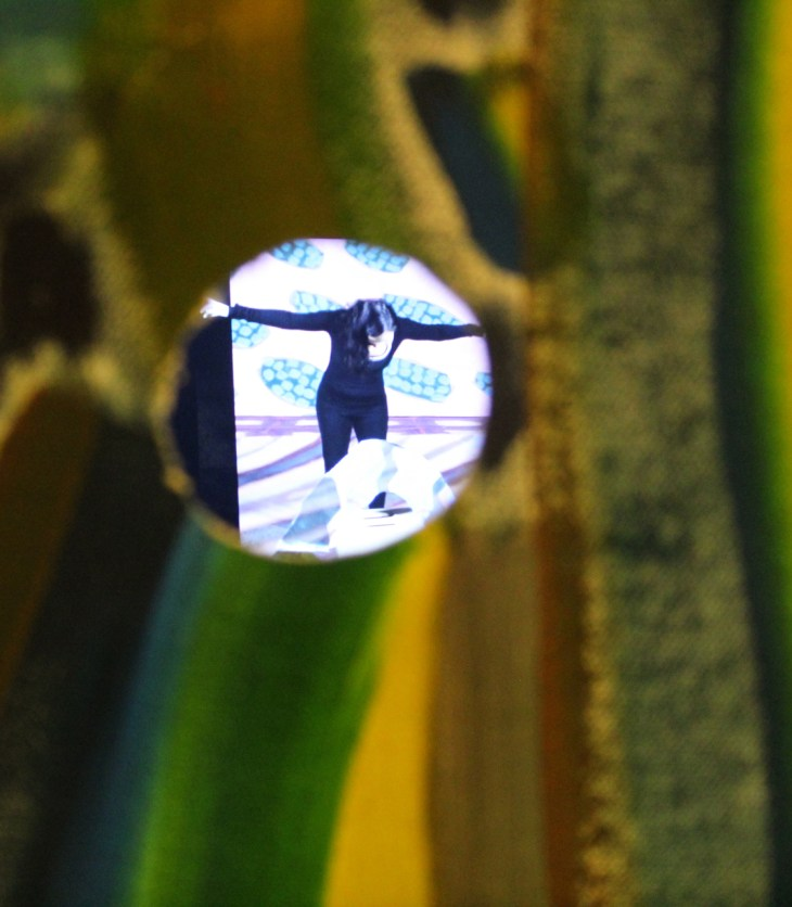 A close-up photograph of a small rectangular box with two eye wholes. The exterior of the box is painted with swaths of green, brown, blue, grey, and yellow paint. The inside of the box, visible through the holes has a small video screen. The moment caught in this photograph shows a person in all black bending over with arms outstretched, as though bowing.