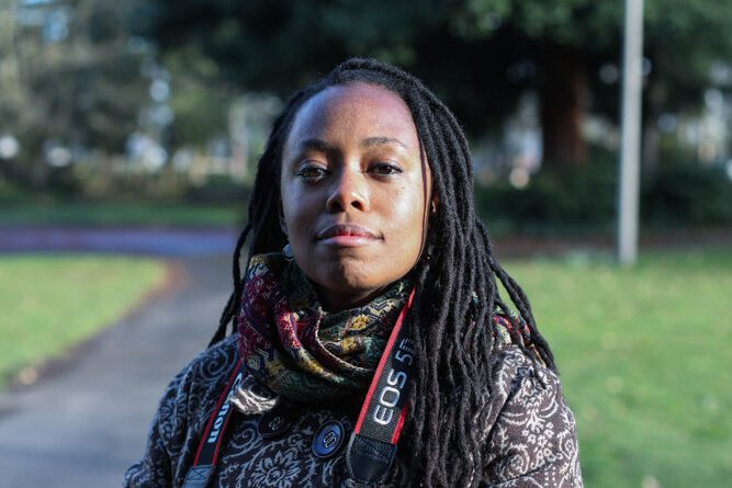 Portrait of Intisar Abioto. She stands in a park carrying a camera with a camera strap around her neck. She looks confidently into the camera with a slight smile. Shes wears a patterned scarf and a patterned jacket. Her long black hair is styled in thin dreads. Sunlight highlights the left side of her face.